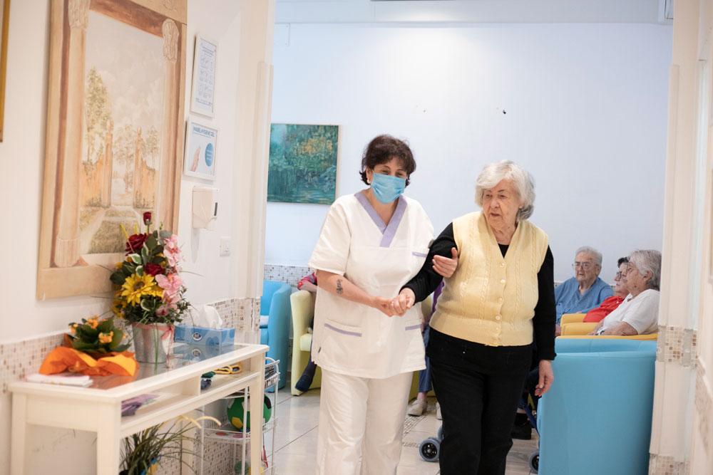 Assistente sanitaria aiuta anziana nella deambulazione