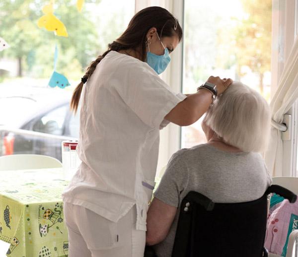 Infermiera da assistenza medica ad una signora anziana