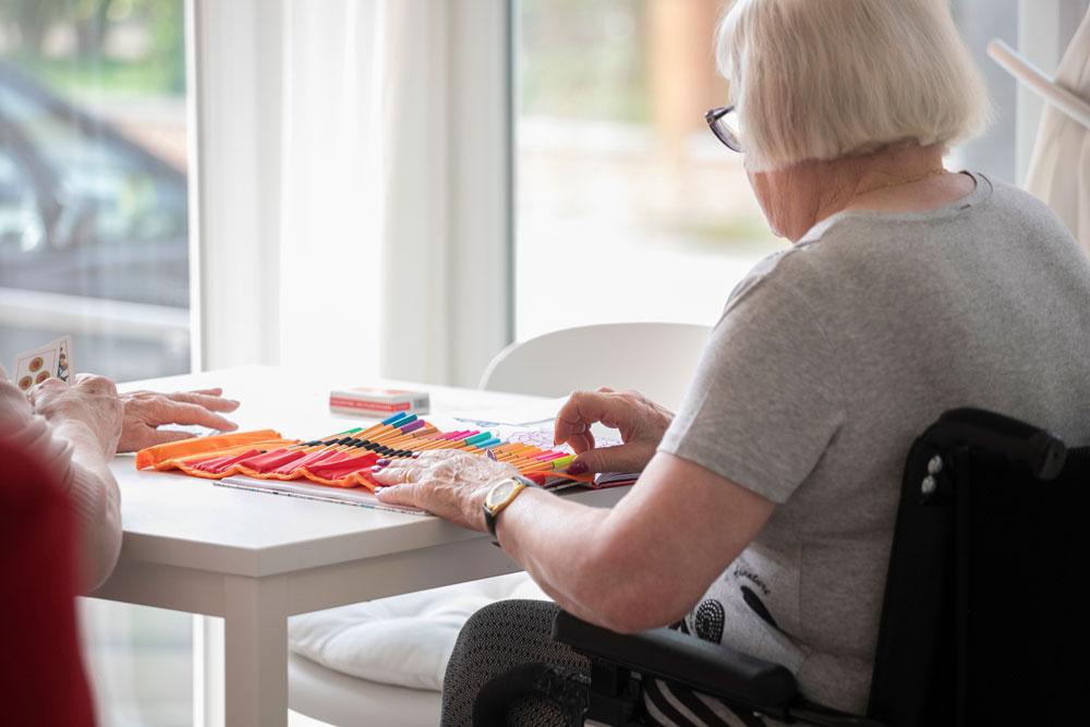 Signora in sedia a rotelle disegna in alloggio anziani